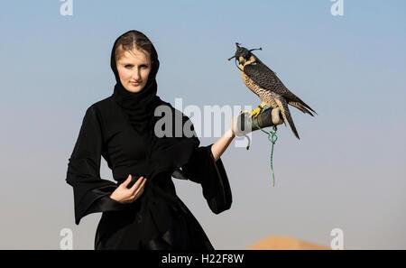 Emirati woman in traditional emirati dress (abaya) with a falcon - Stock Photo