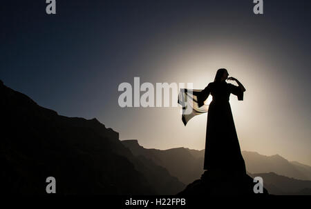 a woman in traditional Emirati dress (abaya) in mountains - Stock Photo