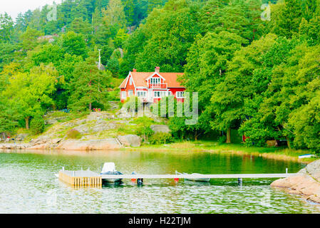 Askeron, Sweden - September 9, 2016: Environmental documentary of red home in coastal woodland. Pier and boats in - Stock Photo