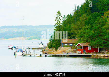 Askeron, Sweden - September 9, 2016: Environmental documentary of small seaside cabins with piers and boats. Coastal - Stock Photo