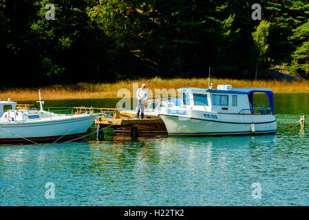 Askeron, Sweden - September 9, 2016: Environmental documentary of senior man standing on pier while fishing. Forest - Stock Photo