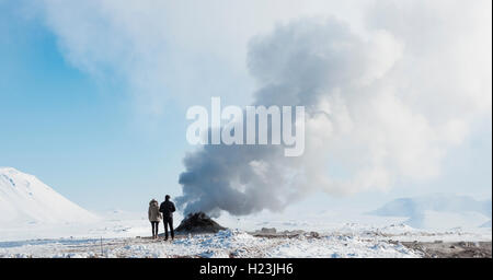 Two tourists standing beside steaming fumarole, solfatara in Hverarönd, also Hverir or Namaskard, geothermal area - Stock Photo