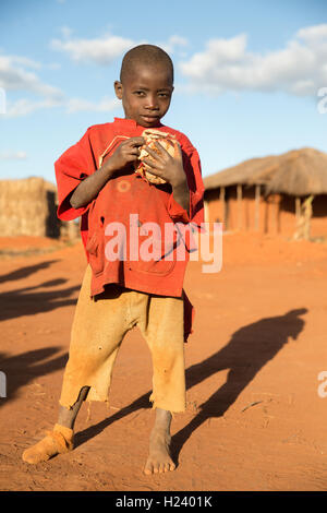 Namina village, Nampula Province, Mozambique, August 2015: A young boy holds a ball he hand his friends have been - Stock Photo