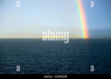 Seascape view of spectrum colours in rainbow over sea and island, Norway - Stock Photo