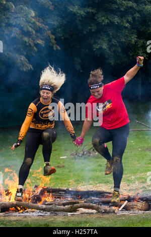 Friends holding hands jumping fire at Bear Grylls Survival Race, Tatton Park, Knutsford,  Competitors, leaping at - Stock Photo