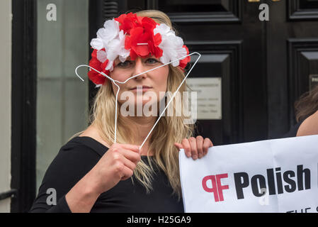 London, UK. 24th Sep, 2016. A Polish feminist stands holding coathangers at the protest at the Polish Embassy in - Stock Photo