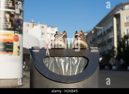 Shoes on a garbage can - Stock Photo