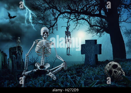 Nighttime Halloween scene with skeletons at a cemetery and the silhouette of a dead tree in the blue moonlight - Stock Photo