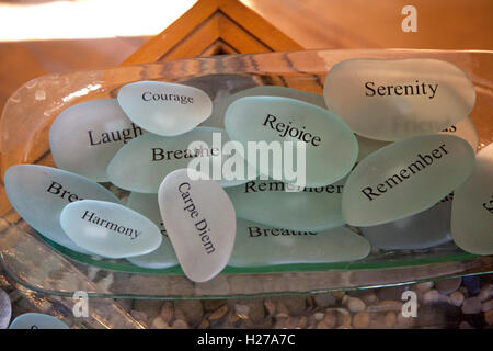 Engraved smooth oval stones with encouraging words of wisdom on each stone in the Stone's Throw shop. Bayfield Wisconsin - Stock Photo