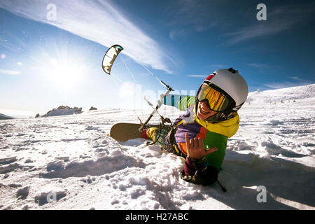 Snowboarder skydives on blue sky backdrop in mountains snowfall - Stock Photo