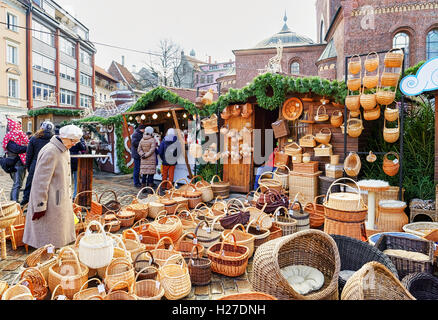 Riga, Latvia - December 25, 2015: Old latvian lady looking at the straw baskets at one of the stalls during the - Stock Photo