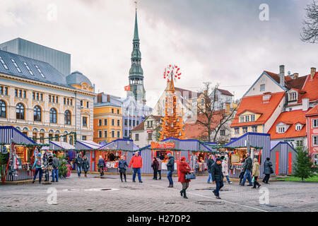 Riga, Latvia - December 26, 2015: Random people taking a walk around the Christmas market located on Livu square - Stock Photo