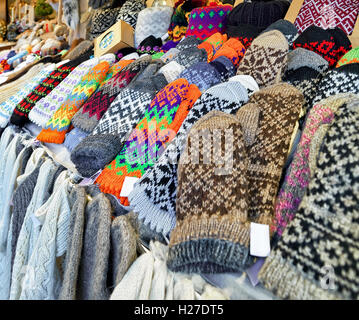 Warm colorful mittens, gloves, socks and hats at one of the stalls at the Christmas Market in Riga, Latvia. The - Stock Photo