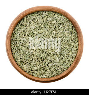 Fennel seeds in a wooden bowl on white background. Dried fruits of Foeniculum vulgare, an aromatic and flavorful - Stock Photo