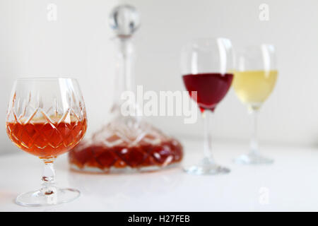 Brandy or cognac in cut glass goblet with decanter with white and red wine - Stock Photo