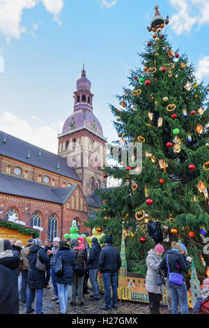 Riga, Latvia - December 25, 2015: People near the Christmas tree at the Christmas market in the Dome square in the - Stock Photo