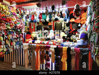 Warm colorful mittens, gloves, socks and hats at one of the stalls at the street Christmas Market in Riga, Latvia. - Stock Photo