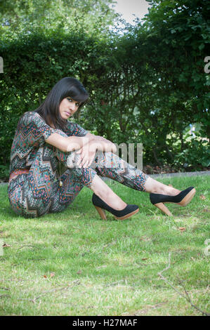 Beautiful Indian woman sat on the grass staring