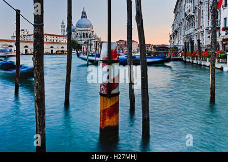 Low point view over Grand Canal waters towards Di Santa Maria cathedral in Venice at sunset. Poles for Gondola standing - Stock Photo