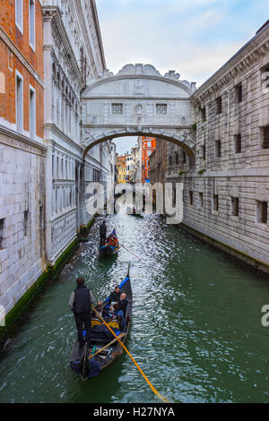 ITALY, VENICE - APRIL 2, 2016: Gondolier on gondola on the Bridge of Sight taking tourist for a ride. View of the - Stock Photo