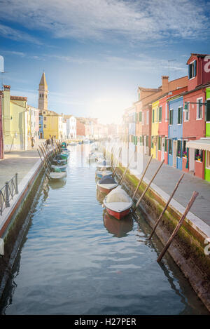 Unusually painted buildings, boats parked in the canals, the town of Burano. - Stock Photo