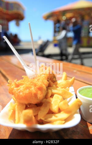 Traditional fish, chips, and a side of mushy peas, on the Brighton seafront, in East Sussex, England, UK - Stock Photo