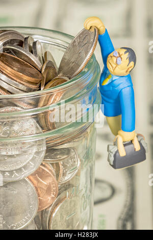 Jar filled with coins shows and little man hanging on - Stock Photo