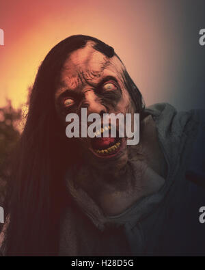 A closeup of a scary dead zombie momster outside for a halloween, fear or death concept. - Stock Photo