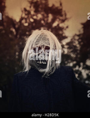 A white scary ghost zombie is outside at night with trees in the background for a decoration or halloween concept. - Stock Photo