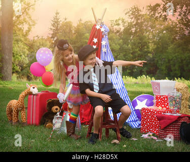Two children are playing outside dressing up as carnival people at a circus party for an imagination or creativity - Stock Photo