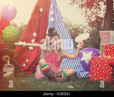 A little child is pretending to perform at a circus theme background with party balloons for an imagination, art - Stock Photo