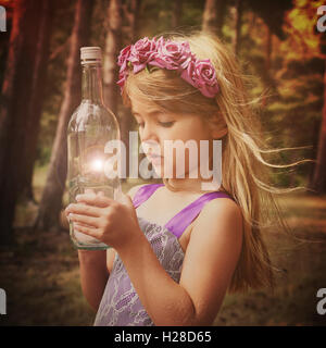 A little fairy girl is in the woods with looking at a magical bottle for an imagination or fantasy concept. - Stock Photo