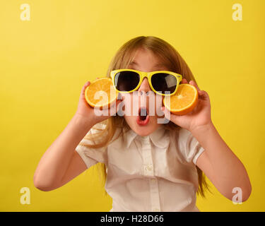 A girl is holding a juicy fruit orange on an isolated yellow background. The child is wearing glasses with a funny - Stock Photo