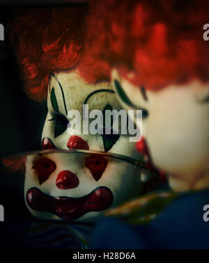 A closeup of a scary evil clown toy doll looking in a broken mirror that could be possessed with evil for a halloween. - Stock Photo