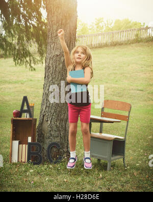 A child is jumping up in happiness outside with a desk and book. Use it for a back to school, education or success - Stock Photo