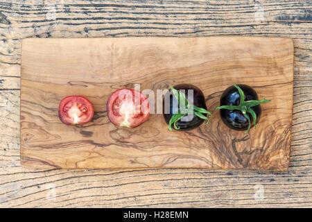 Solanum lycopersicum. Black Tomatoes Indigo Rose whole and halved on wood - Stock Photo