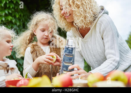 Family rub apples for baking a cake together - Stock Photo