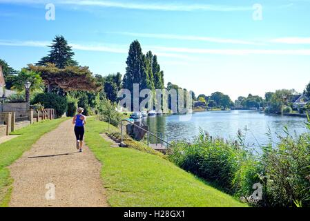 Young woman running on the towpath at Penton Hook Laleham Surrey - Stock Photo