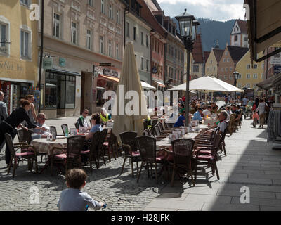 Füssen, Germany - April 04, 2016: summer street scene in the pedestrian zone with outdoor cafe's and strolling vacationer - Stock Photo