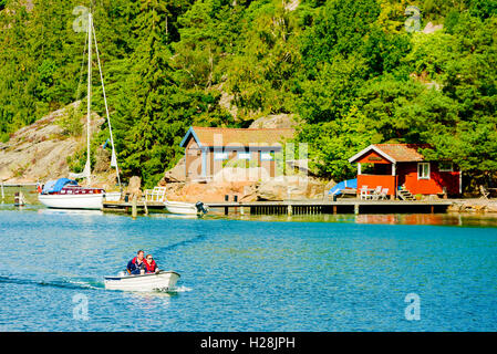 Askeron, Sweden - September 9, 2016: Environmental documentary of adult couple traveling in small open motorboat - Stock Photo