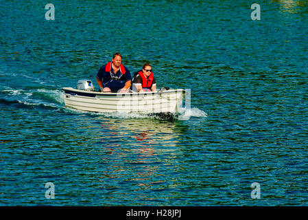 Askeron, Sweden - September 9, 2016: Environmental documentary of adult couple traveling in small open motorboat. - Stock Photo