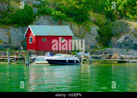 Askeron, Sweden - September 9, 2016: Environmental documentary of red boathouse on island with leisure boats in - Stock Photo