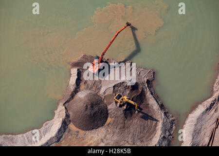 aerial view of two diggers working next to a lagoon in a quarry in Yorkshire, UK - Stock Photo