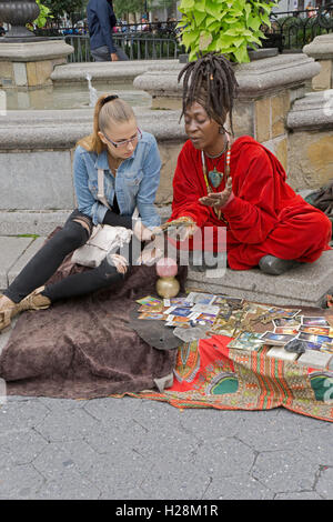 A psychic arot card reading in Union Square Park in Manhattan, New York City - Stock Photo