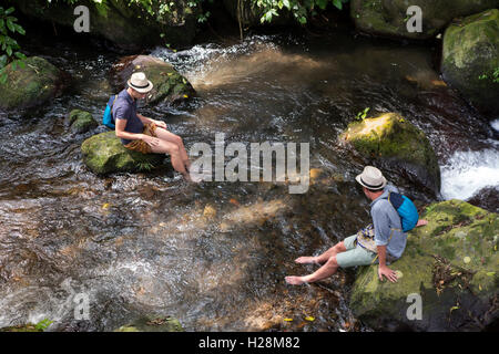 Indonesia, Bali, Tampaksiring, Gunung Kawi Temple complex, tourists cooling feet in Pakerisan River - Stock Photo