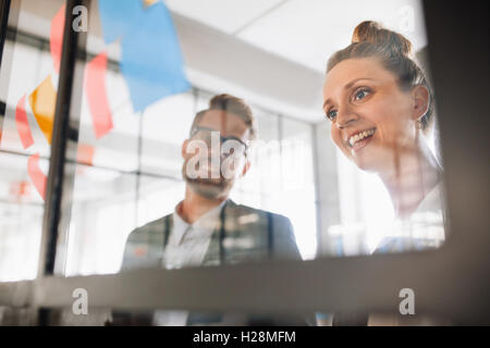 Portrait of two young professionals looking over adhesive notes on glass wall and brainstorming. Young man and women - Stock Photo