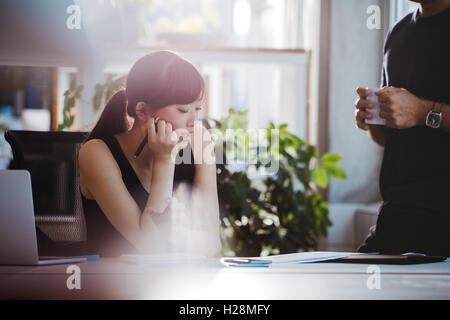 Shot of young woman sitting at her desk and talking with male colleague standing by. Coworkers working together - Stock Photo