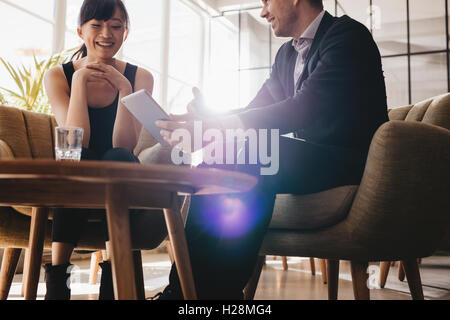 Two corporate colleagues discussing business ideas using digital tablet. Young businessman having meeting with female partner in