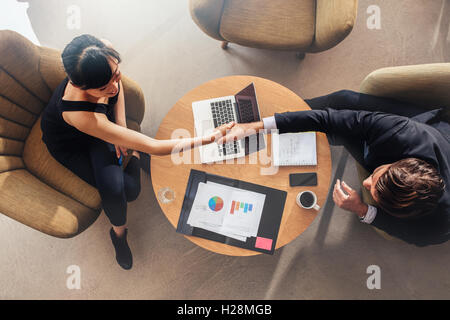 Top view of young business colleagues shaking hands on deal. Charts and laptop on table showing statistics and graphics. - Stock Photo