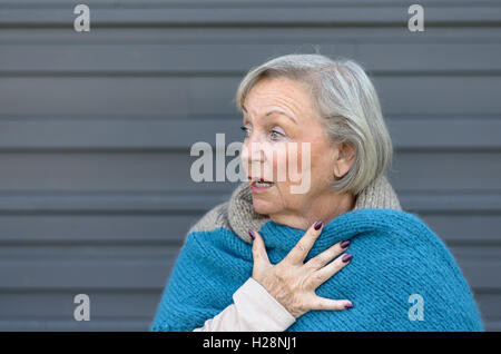 Startled elderly woman clasping her chest in astonishment looking off to the side with a shocked expression and - Stock Photo